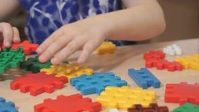 Χέρια του άγνωστου παιχνιδιού κοριτσιών με το δομικό έτοιμο σύστημα απόθεμα βίντεο