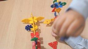 Χέρια του άγνωστου παιχνιδιού παιδιών με το δομικό έτοιμο σύστημα απόθεμα βίντεο