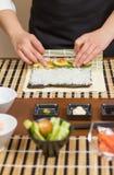 Χέρια του αρχιμάγειρα γυναικών που κυλούν επάνω ένα ιαπωνικό σούσι Στοκ Εικόνες