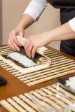 Χέρια του αρχιμάγειρα γυναικών που κυλούν επάνω ένα ιαπωνικό σούσι Στοκ Εικόνα