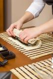 Χέρια του αρχιμάγειρα γυναικών που κυλούν επάνω ένα ιαπωνικό σούσι Στοκ Φωτογραφία