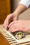 Χέρια του αρχιμάγειρα γυναικών που κυλούν επάνω ένα ιαπωνικό σούσι Στοκ Φωτογραφίες