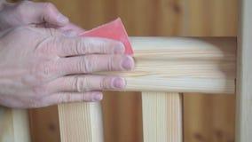 Χέρια του ατόμου που γυαλίζουν την ξύλινη ράγα χεριών με το έγγραφο άμμου απόθεμα βίντεο