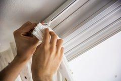 Χέρια του ατόμου που εγκαθιστά τις κουρτίνες πέρα από το παράθυρο Στοκ εικόνα με δικαίωμα ελεύθερης χρήσης