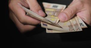 Χέρια του ατόμου που μετρούν 50 πενήντα ευρώ φιλμ μικρού μήκους