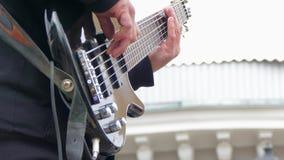 Χέρια του ατόμου που παίζει την ηλεκτρική βαθιά κιθάρα απόθεμα βίντεο