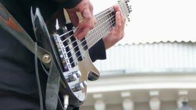 Χέρια του ατόμου που παίζει την ηλεκτρική βαθιά κιθάρα φιλμ μικρού μήκους