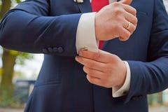 Χέρια του γαμήλιου νεόνυμφου που παίρνουν έτοιμα στο κοστούμι Στοκ φωτογραφίες με δικαίωμα ελεύθερης χρήσης