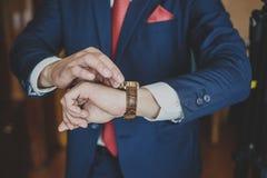 Χέρια του γαμήλιου νεόνυμφου που παίρνουν έτοιμα στο κοστούμι Στοκ Εικόνα