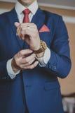 Χέρια του γαμήλιου νεόνυμφου που παίρνουν έτοιμα στο κοστούμι Στοκ Φωτογραφίες