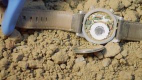 Χέρια του εμπειρογνώμονα στα γάντια λατέξ που βρήκαν και σκάβουν από την άμμο wristwatch του θύματος μετά από τη συντριβή αεροπλά απόθεμα βίντεο