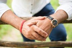 Χέρια του ενήλικων αρσενικών φορώντας ρολογιού και του βραχιολιού Στοκ εικόνες με δικαίωμα ελεύθερης χρήσης