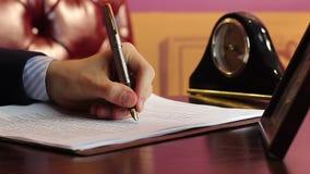 Χέρια του επιχειρηματία κινηματογραφήσεων σε πρώτο πλάνο που υπογράφουν τα έγγραφα στο γραφείο απόθεμα βίντεο