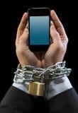 Χέρια του επιχειρηματία που εθίζονται στην αλυσίδα εργασίας που κλειδώνεται στον κινητό τηλεφωνικό εθισμό Στοκ Φωτογραφία