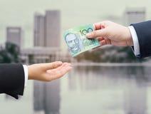 Χέρια του επιχειρηματία που περνούν το αυστραλιανό τραπεζογραμμάτιο δολαρίων (AUD) Στοκ φωτογραφίες με δικαίωμα ελεύθερης χρήσης