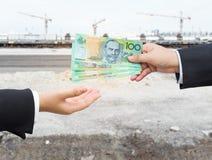 Χέρια του επιχειρηματία που περνούν το αυστραλιανό τραπεζογραμμάτιο δολαρίων (AUD) Στοκ φωτογραφία με δικαίωμα ελεύθερης χρήσης