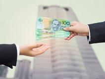 Χέρια του επιχειρηματία που περνούν το αυστραλιανό τραπεζογραμμάτιο δολαρίων (AUD) Στοκ Φωτογραφία