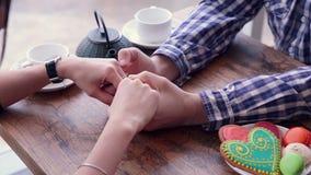 Χέρια του ευτυχούς αγαπώντας ζεύγους Ήπια χάδι, τρίψιμο Μπισκότα και τσάι στον πίνακα φιλμ μικρού μήκους