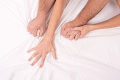 Χέρια του ζεύγους που που κάνει την αγάπη στο κρεβάτι στο άσπρο τσαλακωμένο φύλλο, εστίαση σε ετοιμότητα στοκ φωτογραφία