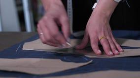Χέρια του θηλυκού επισημαίνοντας σχεδίου ραφτών στο ύφασμα φιλμ μικρού μήκους