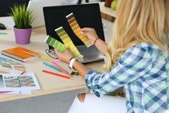 Χέρια του θηλυκού σχεδιαστή στο γραφείο που λειτουργεί με τα δείγματα χρώματος Στοκ φωτογραφία με δικαίωμα ελεύθερης χρήσης