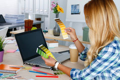 Χέρια του θηλυκού σχεδιαστή στο γραφείο που λειτουργεί με τα δείγματα χρώματος Στοκ Εικόνες