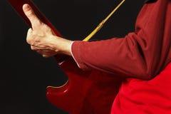 Χέρια του καλλιτέχνη που παίζει την κιθάρα στο σκοτεινό υπόβαθρο Στοκ Φωτογραφία