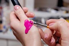 Χέρια του καλλιτέχνη makeup που εξετάζει ένα ρόδινο υγρό κραγιόν στοκ φωτογραφία