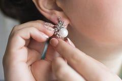 Χέρια του κοριτσιού που φορούν τα σκουλαρίκια μαργαριταριών στοκ εικόνα