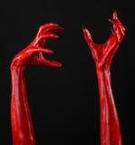 Χέρια του κόκκινου διαβόλου με τα μαύρα καρφιά, κόκκινα χέρια της Satan, θέμα αποκριών, σε ένα μαύρο υπόβαθρο, που απομονώνεται Στοκ Φωτογραφίες