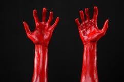 Χέρια του κόκκινου διαβόλου με τα μαύρα καρφιά, κόκκινα χέρια της Satan, θέμα αποκριών, σε ένα μαύρο υπόβαθρο, που απομονώνεται Στοκ εικόνες με δικαίωμα ελεύθερης χρήσης