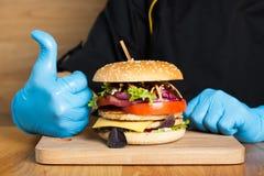 Χέρια του μάγειρα με burger Στοκ φωτογραφία με δικαίωμα ελεύθερης χρήσης
