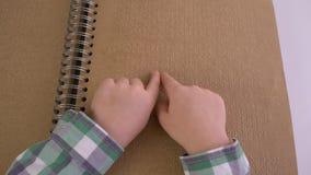Χέρια του με οπτική αναπηρία διαβασμένου παιδί βιβλίου μπράιγ με την πηγή χαρακτήρων φιλμ μικρού μήκους