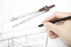 Χέρια του μηχανικού που λειτουργούν σε ένα σχέδιο κατασκευής Στοκ φωτογραφία με δικαίωμα ελεύθερης χρήσης