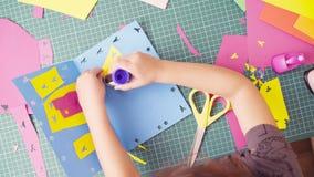 Χέρια του μικρού κοριτσιού που κολλά το χρωματισμένο έγγραφο απόθεμα βίντεο