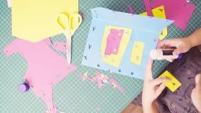 Χέρια του μικρού κοριτσιού που κολλά το χρωματισμένο έγγραφο φιλμ μικρού μήκους