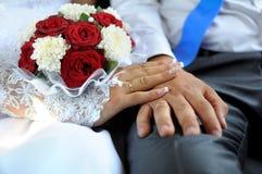 Χέρια του νεόνυμφου και της νύφης με τα γαμήλια δαχτυλίδια και ένα weddin Στοκ φωτογραφία με δικαίωμα ελεύθερης χρήσης