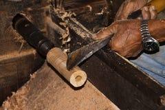 Χέρια του παλαιού εργαζομένου που διαμορφώνει ένα κομμάτι του ξύλου μπαμπού με το εργαλείο μετάλλων σε ένα εργοστάσιο ομπρελών χα στοκ εικόνα με δικαίωμα ελεύθερης χρήσης