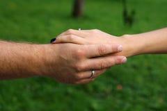 Χέρια του παντρεμένου ζευγαριού στο πάρκο Στοκ Εικόνα