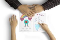 Χέρια του πατέρα και του παιδιού με τη ευχετήρια κάρτα στοκ φωτογραφία