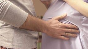 Χέρια του συζύγου στο tummy της έγκυου συζύγου του ο σύζυγος κτύπησε tenderly την έγκυο κοιλιά της συζύγου του Νεαρός άνδρας Στοκ φωτογραφία με δικαίωμα ελεύθερης χρήσης