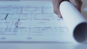 Χέρια του σχεδίου ανοίγματος αρχιτεκτόνων των νέων οδηγιών οικοδόμησης, γραφείο σχεδίου απόθεμα βίντεο