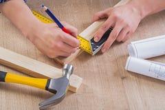 Χέρια του σχεδίου ξυλουργών με το μολύβι ξύλινο Στοκ Εικόνες