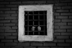 Χέρια του φυλακισμένου πίσω από τους φραγμούς, χρώμα Στοκ φωτογραφία με δικαίωμα ελεύθερης χρήσης