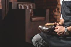 Χέρια του χειροτεχνικού παπουτσιού και του καθαρισμού εκμετάλλευσης του στοκ φωτογραφίες