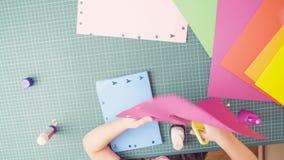 Χέρια του χρωματισμένου κοπή εγγράφου μικρών κοριτσιών με το ψαλίδι απόθεμα βίντεο