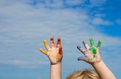Χέρια του χρώματος μωρών ενάντια στο μπλε ουρανό Στοκ εικόνα με δικαίωμα ελεύθερης χρήσης