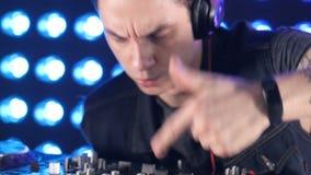 Χέρια του DJ Disco που χρησιμοποιούν τον αναμίκτη και τις περιστροφικές πλάκες στο νυχτερινό κέντρο διασκέδασης απόθεμα βίντεο