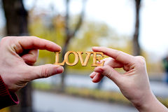 Χέρια των ανδρών και των γυναικών με την αγάπη λέξης Στοκ Εικόνα