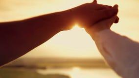 Χέρια των ανδρών και των γυναικών στο ηλιοβασίλεμα φιλμ μικρού μήκους